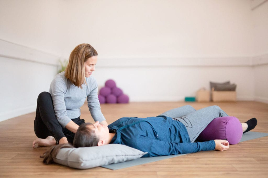 restorative yoga. woman lying down being supported