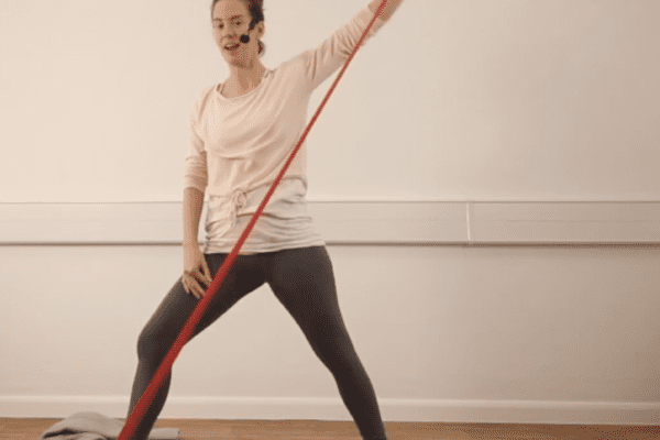 woman doing a warrior two posture with a red resistance band