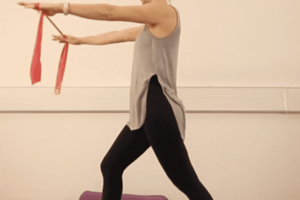 woman doing warrior one yoga posture with a red resistance band