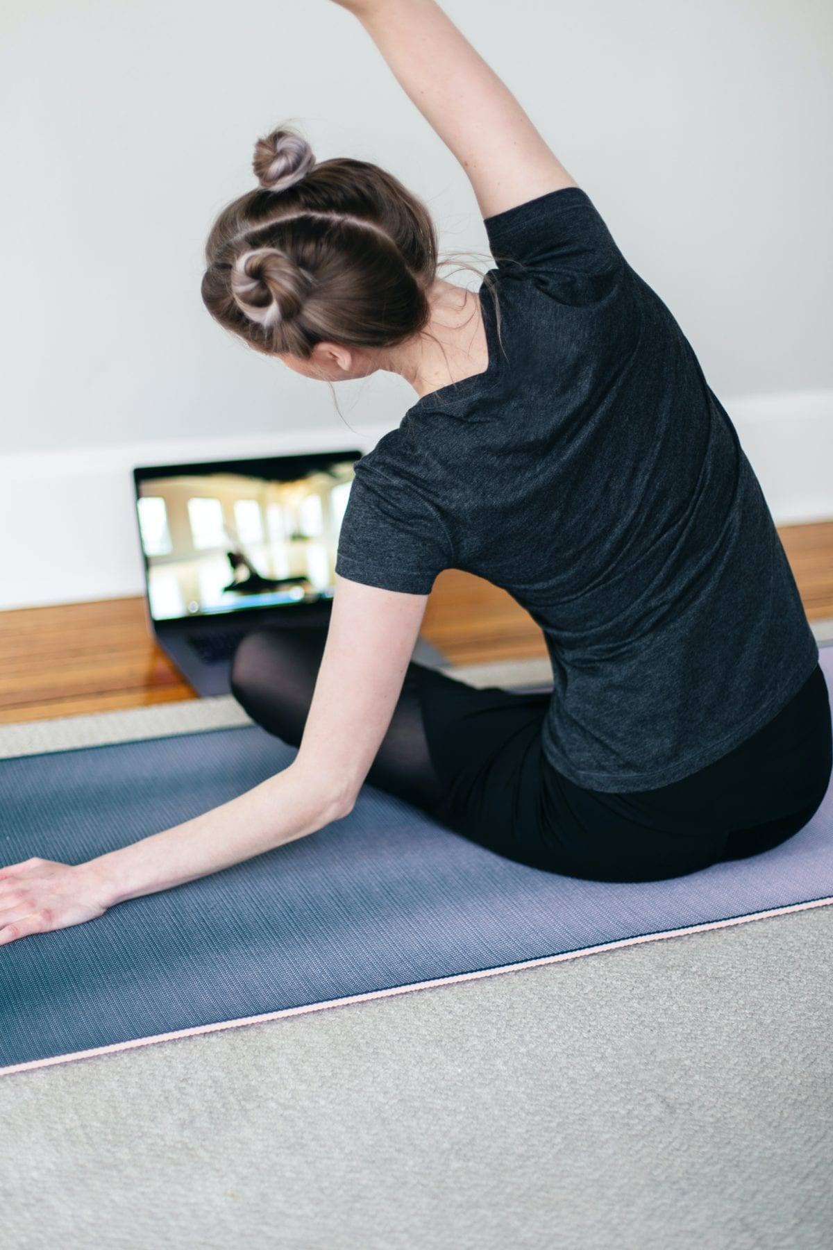 woman doing a seated yoga stretch in front of a laptop